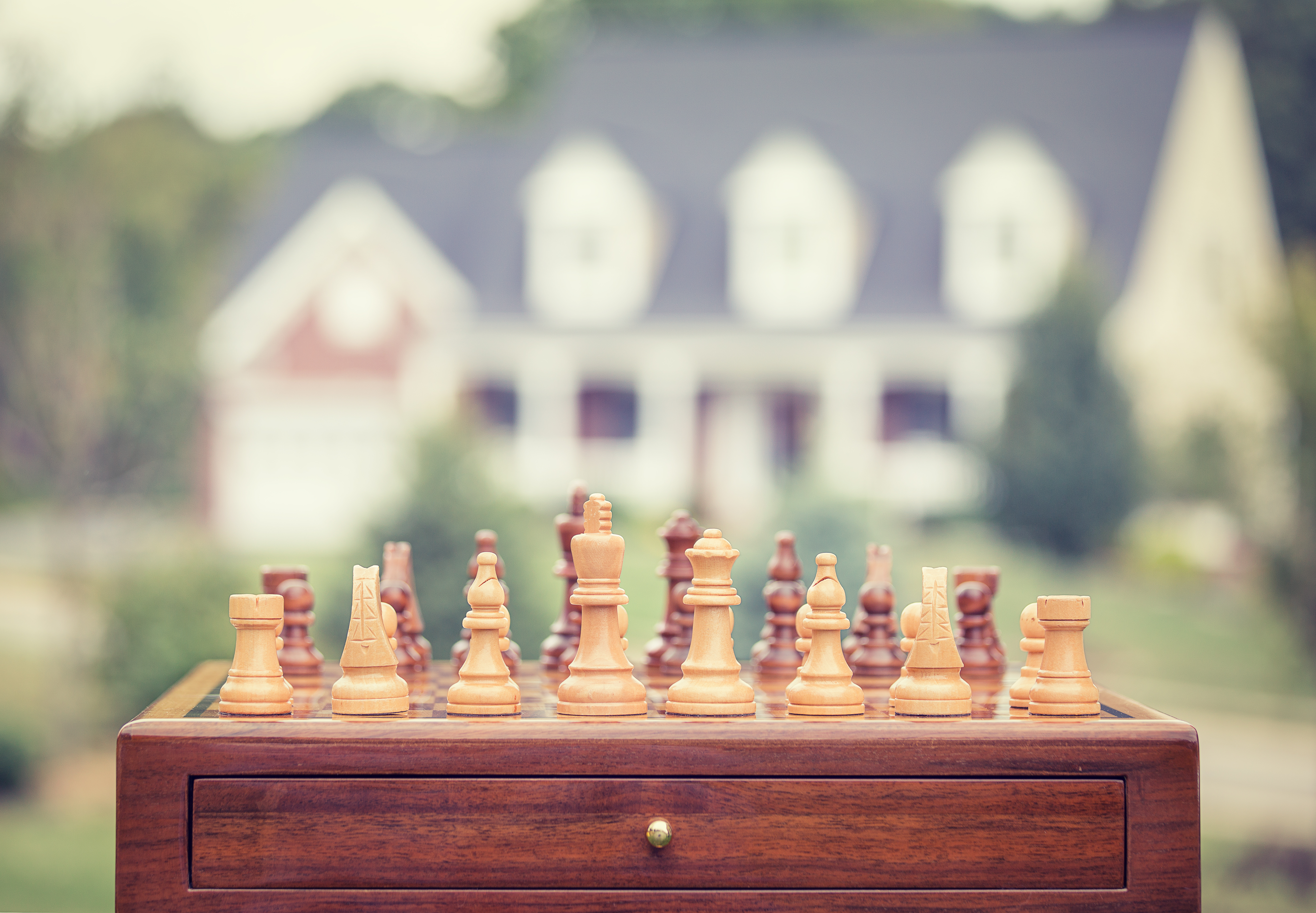 image of a chess boars set in front of a house - represents that you must Choose the Right Property Investing Strategy For You